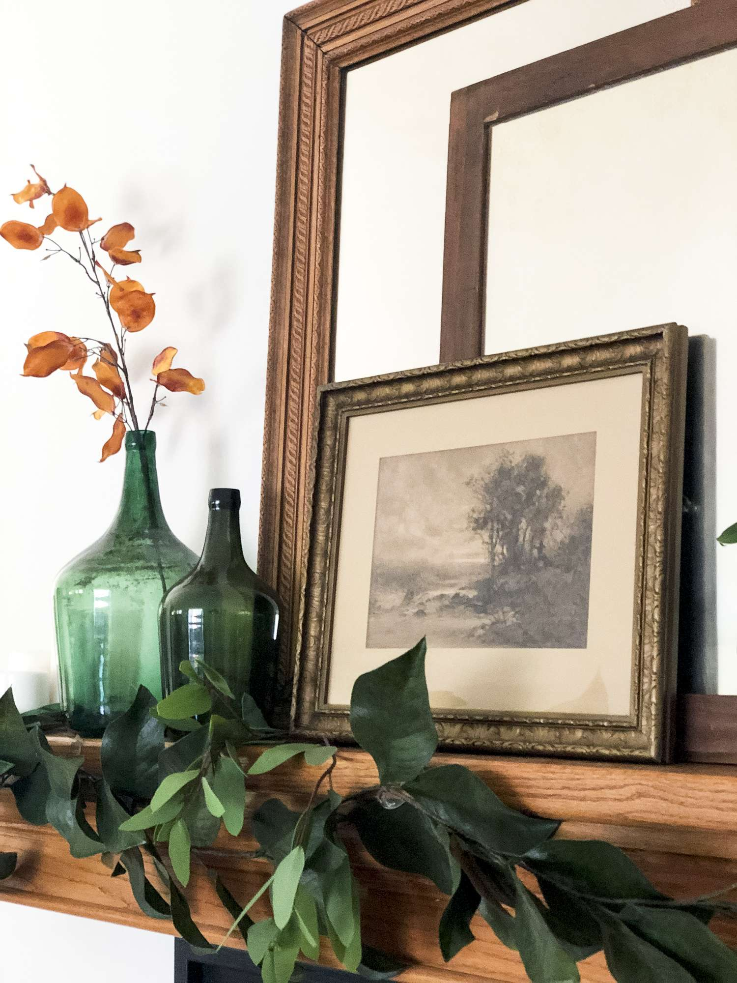 Green demijohn and vintage art pieces on a mantel