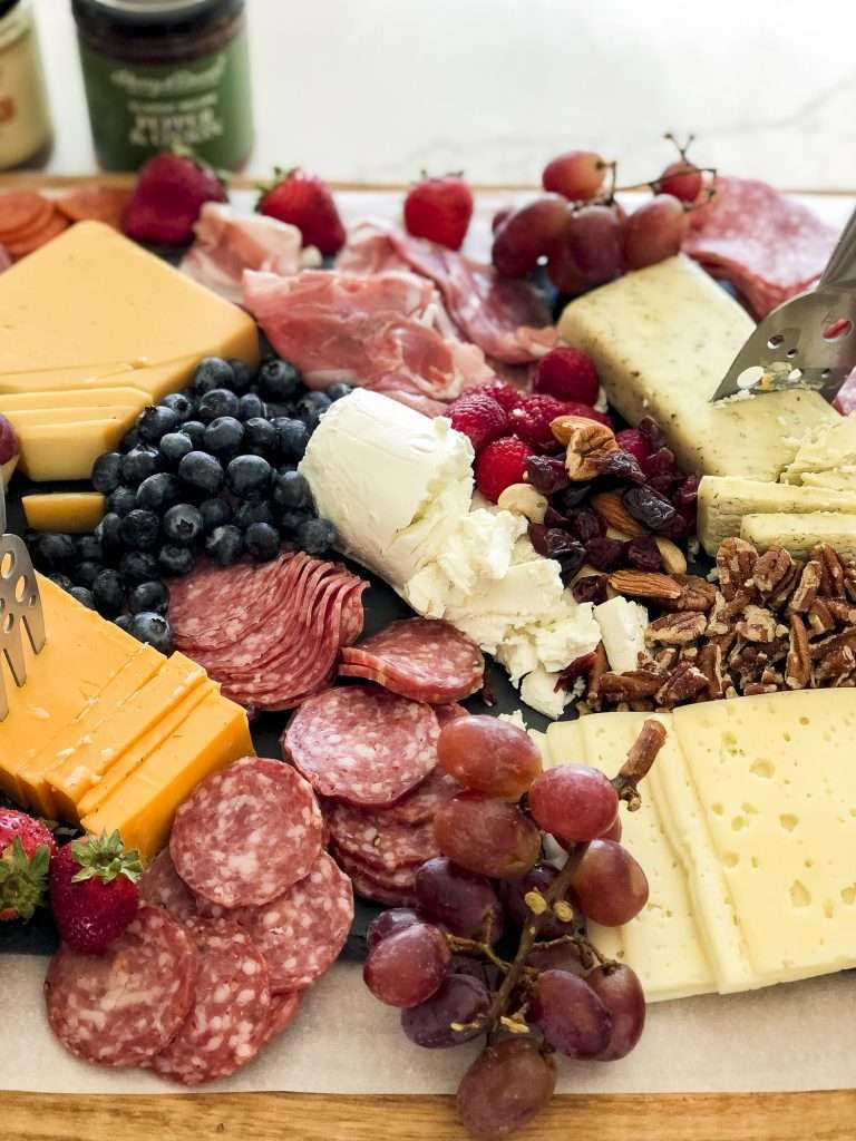 Fruit on a meat and cheese board.