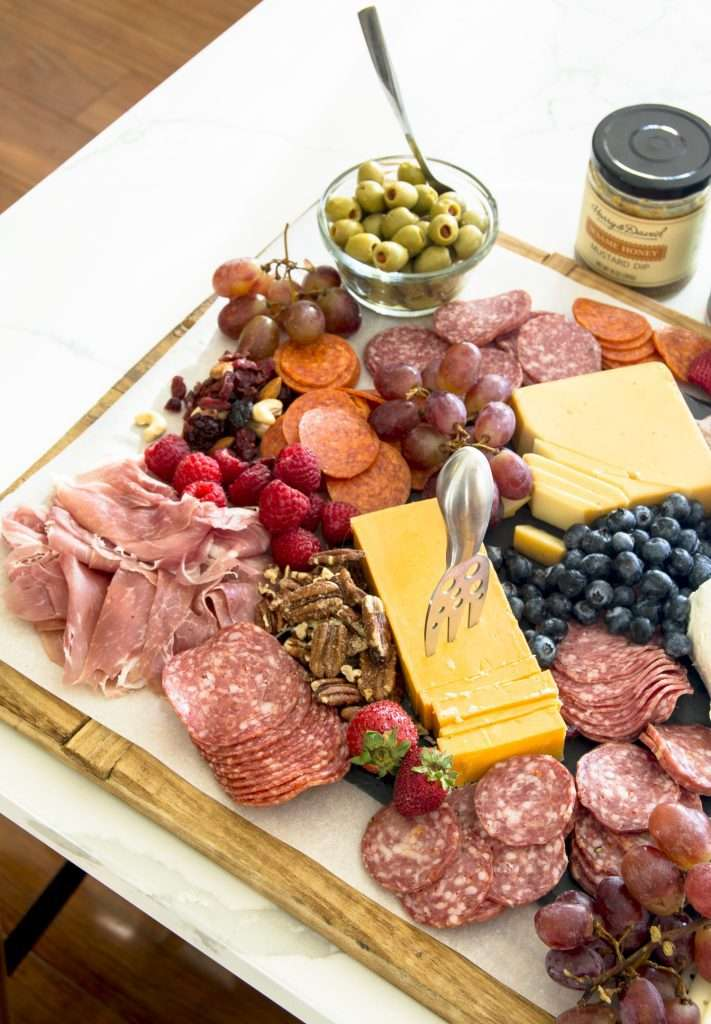 Dish of olives on a meat and cheese board.