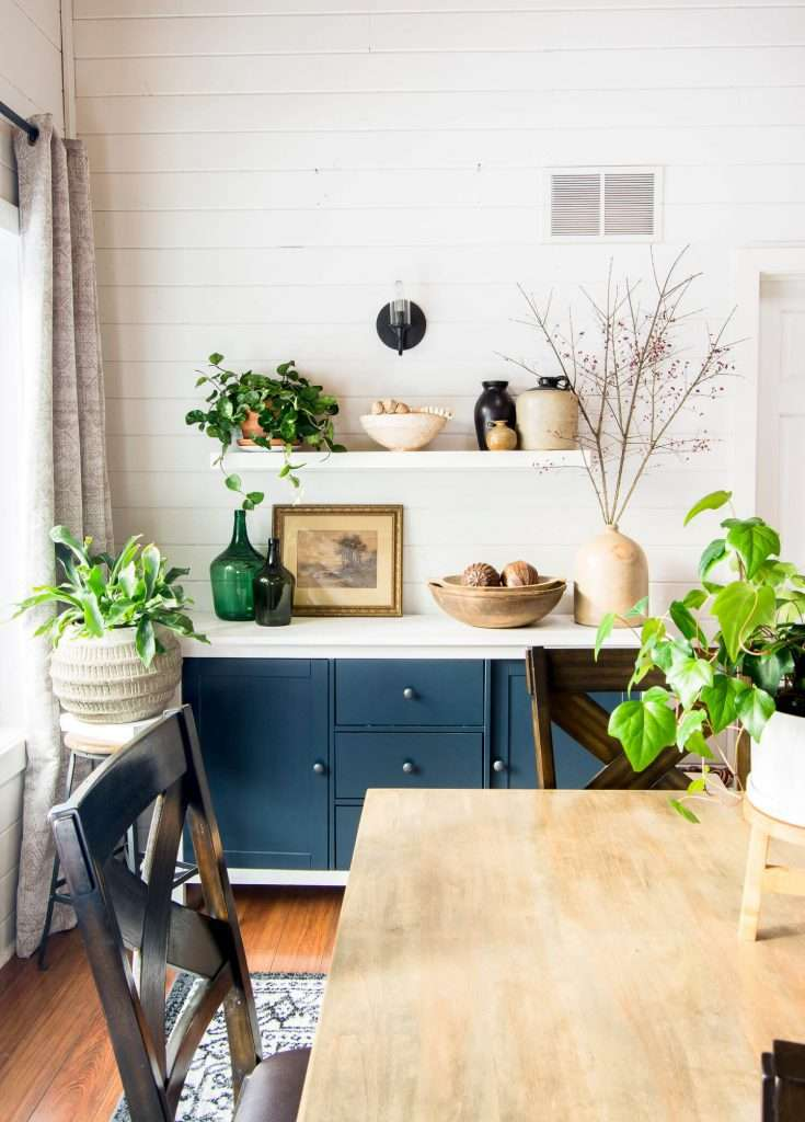 Curated shelf styling in a dining room with vintage pieces.