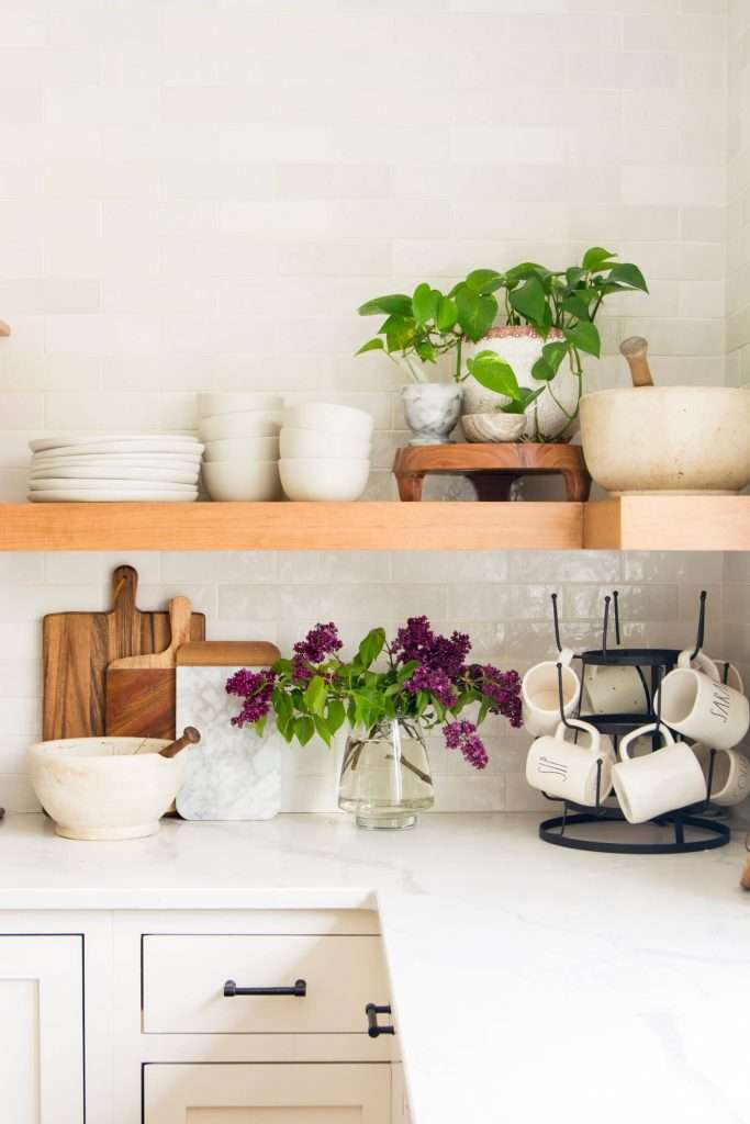 Kitchen shelf styled with houseplants and organic home decor