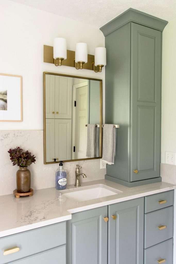 Bathroom vanity cabinet with full height quartz backsplash.