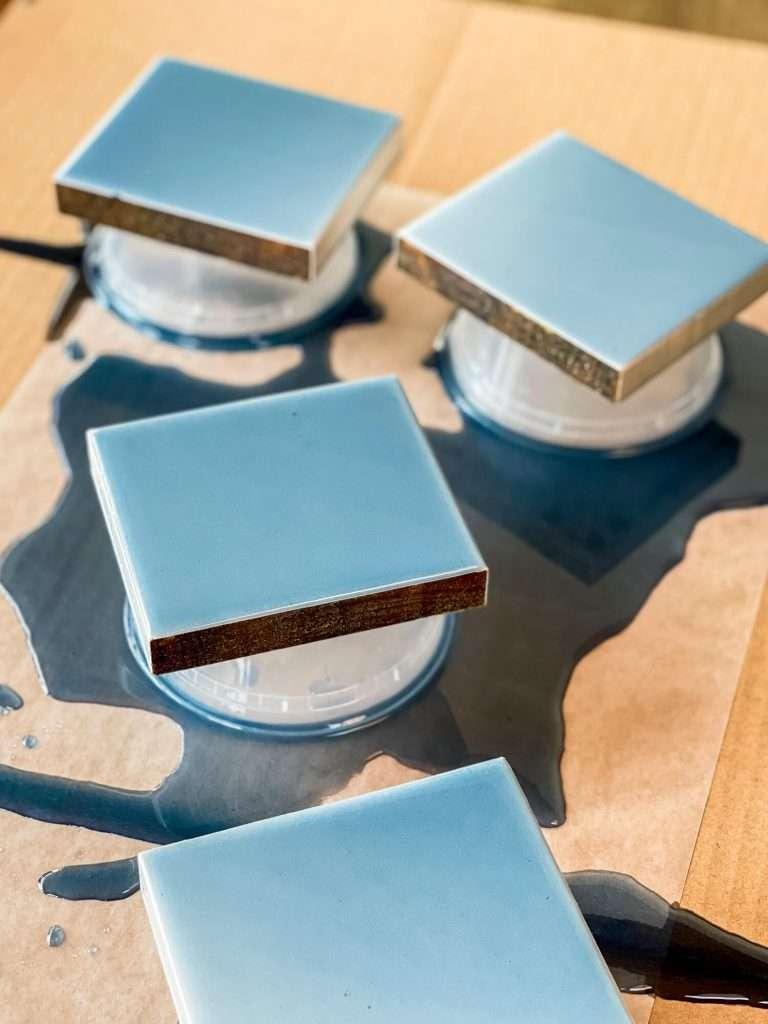 Epoxy resin coasters drying on tupperware.