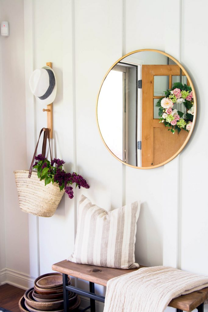 Floor to ceiling board and batten entryway with mirror and decor
