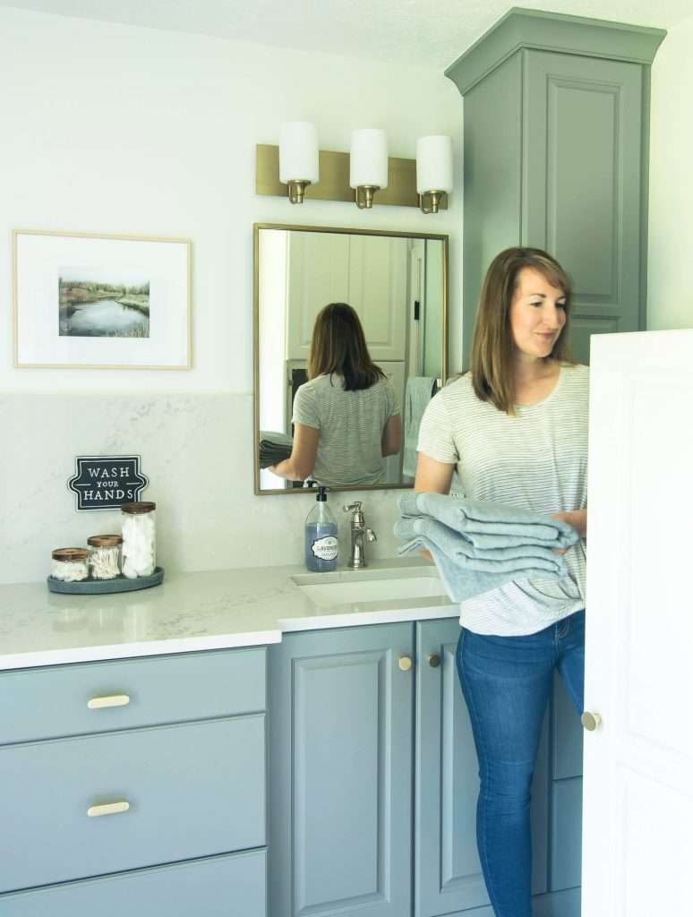 Woman putting towels in bathroom cabinet