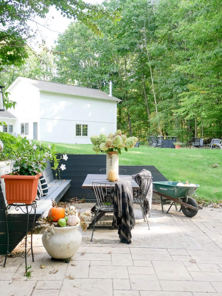 Cozy outdoor spaces with blankets and pumpkins.