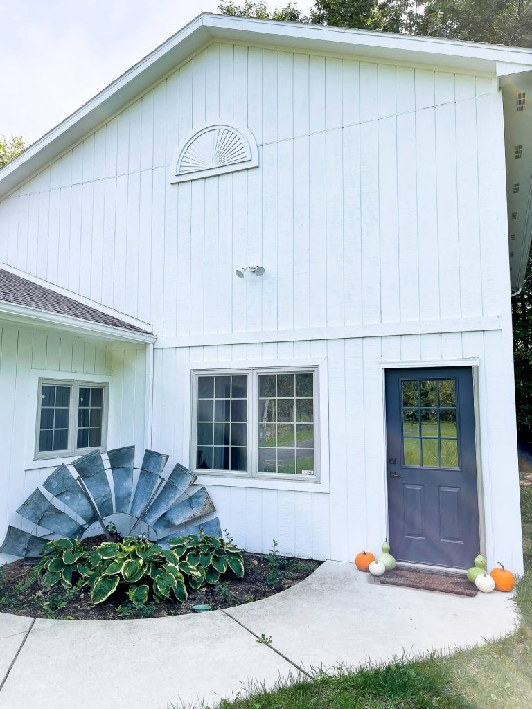 Barn with fall decor by the door.