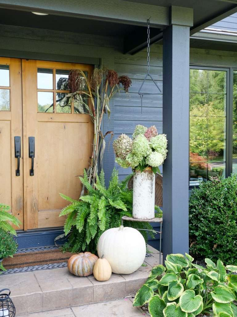 Fall front porch with pumpkins and hydrangeas.