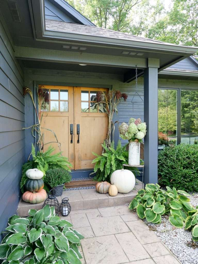 Front porch cozy outdoor space decorated for fall.
