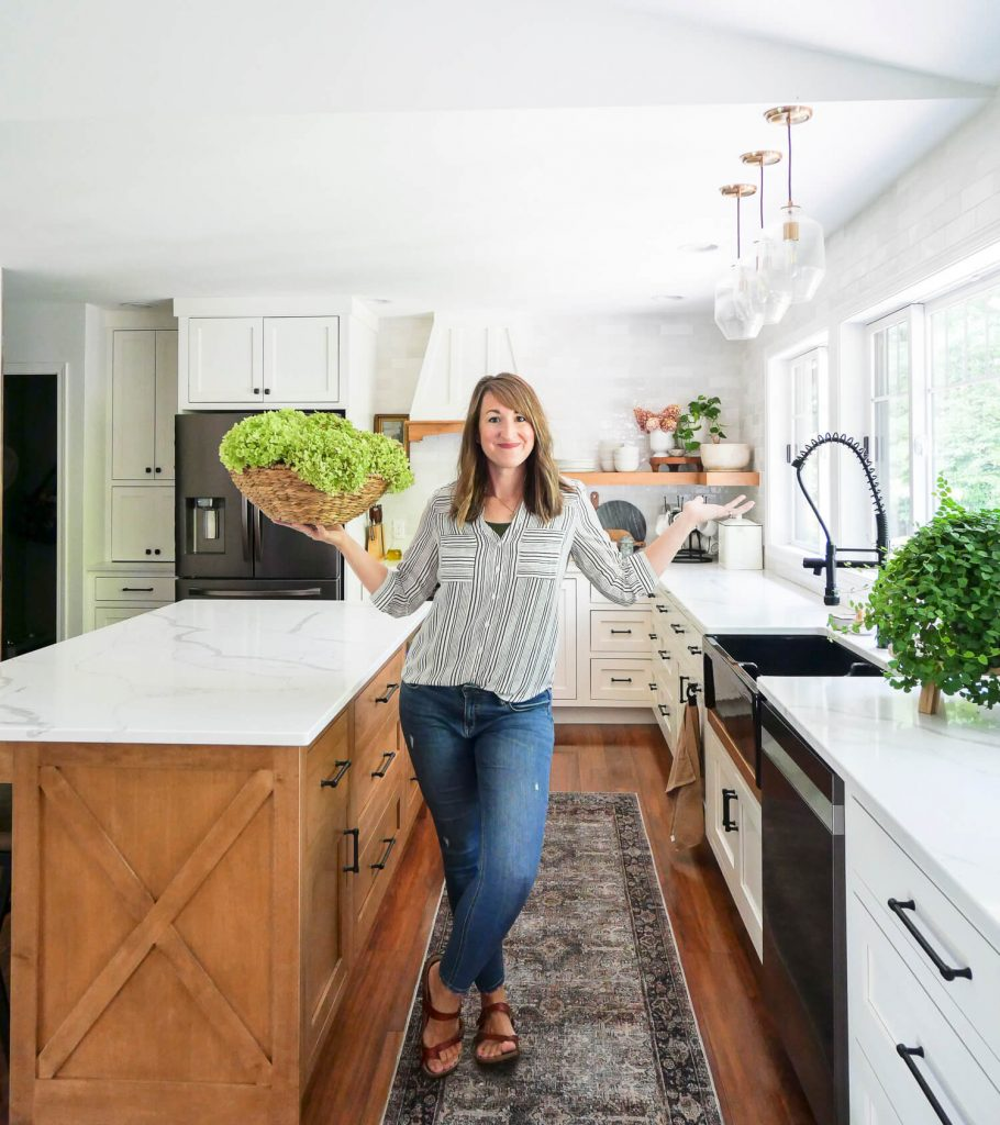 Woman holding dried hydrangeas in a kitchen.